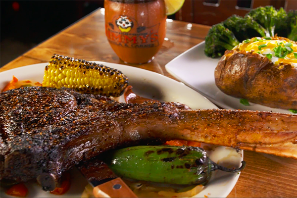 "Jimmy's describes this dish ""so good it should be a crime."" This 32 ounce Tomahawk steak is perfectly seasoned and grilled, and served with grilled corn, jalapenos, sausage, rice, and beans."